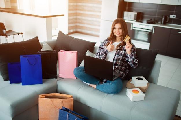 O comprador olha para a tela e possui um cartão de crédito.