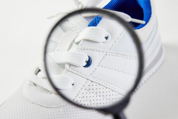 O comprador procura defeitos e detalhes macro nos sapatos com uma lupa. tênis de estilo e moda. descoberta de sapatos respiráveis no buraco.