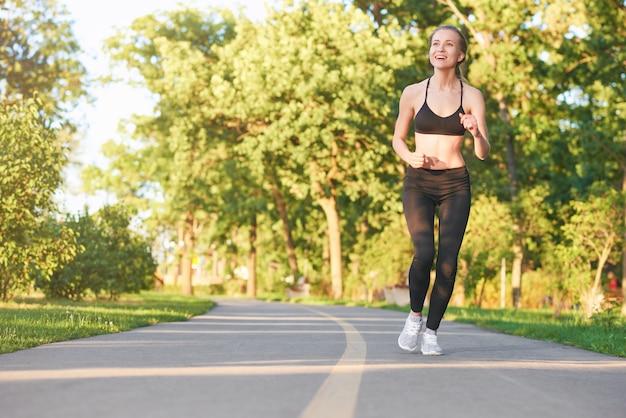 O comprimento total disparou de uma mulher atlética bonita nova que corre na floresta na aptidão do copyspace da manhã ostenta o conceito da positividade dos cuidados médicos da motivação.