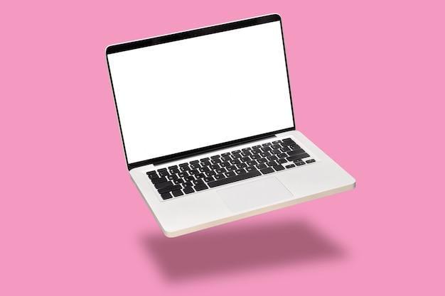 O computador portátil zomba acima com a tela branca vazia vazia isolada no fundo cor-de-rosa.