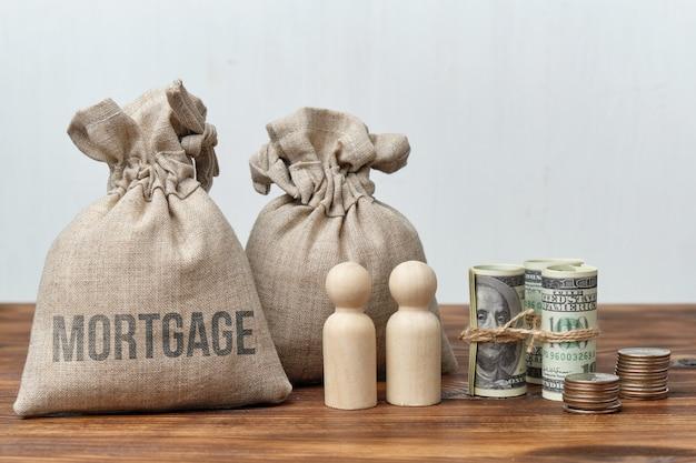 O conceito abstrato de uma hipoteca de sacos de dinheiro e figuras humanas