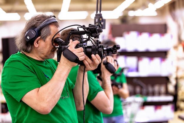 O conceito da criação de tv, conteúdo de vídeo, nos bastidores. uma equipe profissional de cinegrafistas está filmando em câmeras de vídeo. nos bastidores do processo de filmagem do programa de tv. copie o espaço.