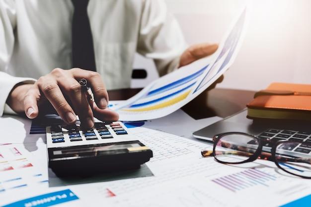 O conceito da finança, homem de negócio analisa a carta do gráfico com utilização do portátil da calculadora e do computador para a previsão de lucro no futuro.