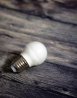 O conceito da ideia. lâmpada em fundo de madeira