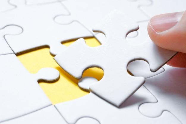 O conceito da imagem completa após o último detalhe. uma peça do quebra-cabeça é segurada por um homem com os dedos