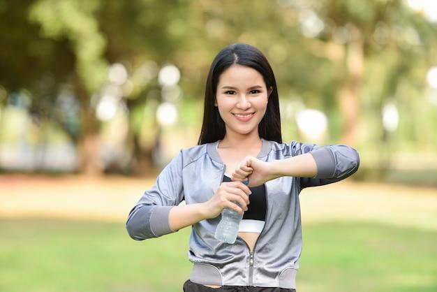 O conceito da saúde da garrafa de água potável da mulher / moça de sorriso relaxa o exercício e guarda a garrafa de água