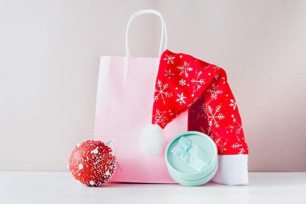 O conceito das vendas de natal. em um fundo bege, uma sacola de papel rosa