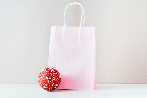 O conceito das vendas de natal. sobre um fundo bege, uma sacola de papel rosa e um balão vermelho de natal.