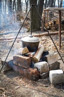O conceito de acampar, em um tripé em cima de um fogo há um pote no qual a comida se prepara em uma pilha de ramos secos