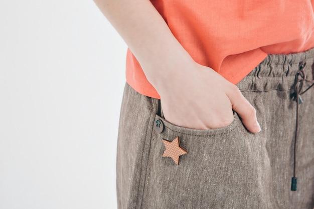 O conceito de acessórios de costura: broche em forma de estrela. mão feminina no bolso closeup