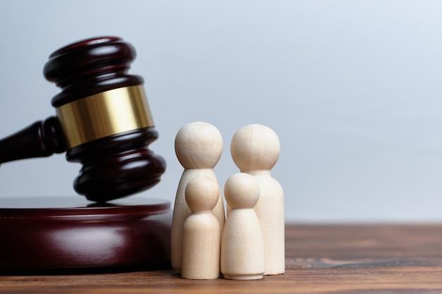 O conceito de adoção de filhos por uma família. o martelo de um juiz com figuras abstratas de pessoas.