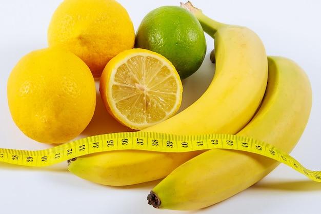 O conceito de alimentação saudável, perda de peso. bananas, limão, fita métrica em cima da mesa.