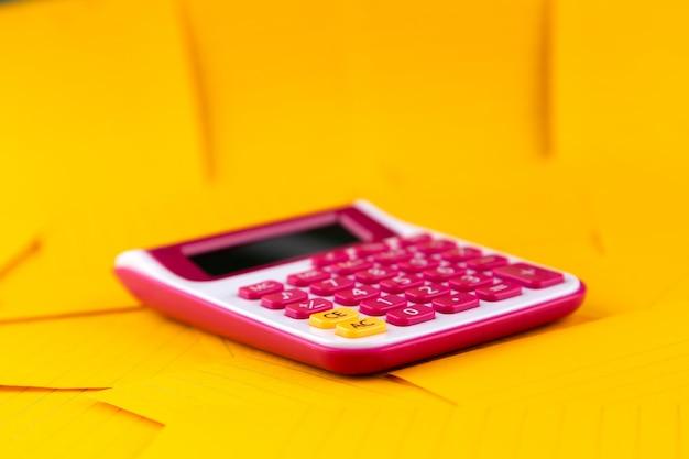 O conceito de análise, análise, cálculos. a calculadora está em folhas de papel laranja.
