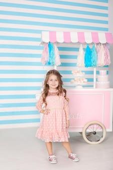 O conceito de aniversário e felicidade - uma menina feliz está de pé em um lindo vestido