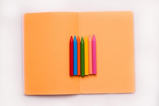 O conceito de ano letivo e desenho. lápis de cera de cores diferentes em um caderno