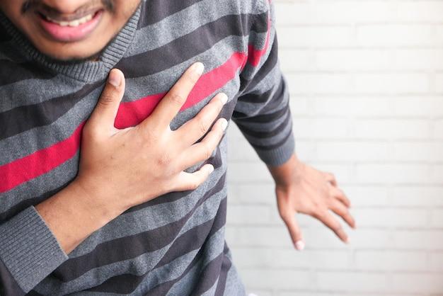 O conceito de ataque cardíaco, homem com dor no coração e segurando o peito com a mão