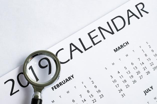O conceito de auditoria financeira em 2019. calendário impresso sob uma lupa.