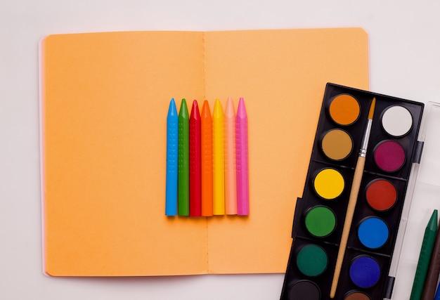 O conceito de aulas de desenho. crayons e tintas de cores diferentes repousam em um caderno