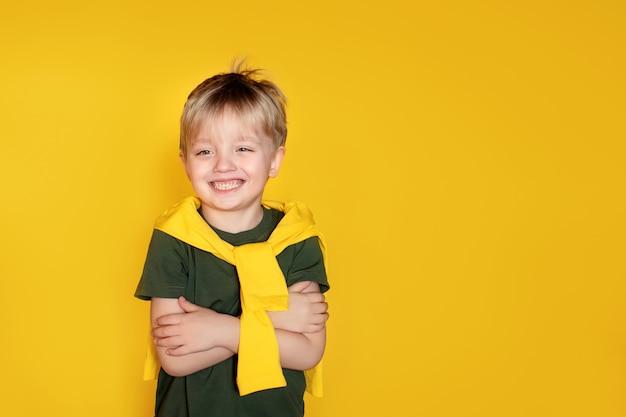 O conceito de bom humor. vibrações positivas. totalmente feliz com o shopping day. eu me sinto legal. garoto bonito 5-6 anos de idade em uma parede amarela.