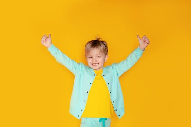 O conceito de bom humor. vibrações positivas. totalmente satisfeito com o shopping day. eu me sinto legal. garoto bonito 5-6 anos de idade em uma parede amarela.