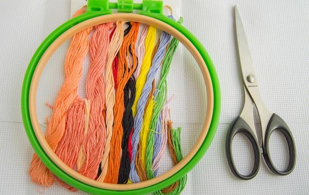 O conceito de bordado. acessórios de costura para tela de bordar, argola, fio dental, configuração plana, vista superior