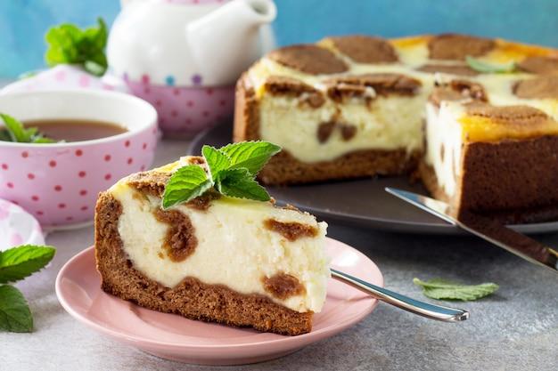 O conceito de café da manhã ou relaxamento cheesecake de chocolate new york e xícara de chá de menta
