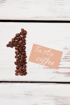 O conceito de café mais saboroso. grãos de café em forma de número um e papel com saborosa frase de café em madeira branca.