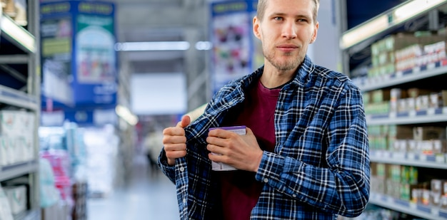 O conceito de cleptomania, um homem na mercearia roubando comida e colocá-la no bolso