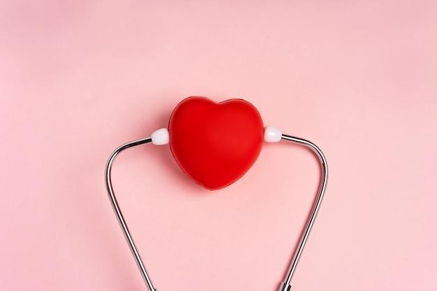 O conceito de comemorar o dia do médico com um estetoscópio e um coração em um fundo rosa