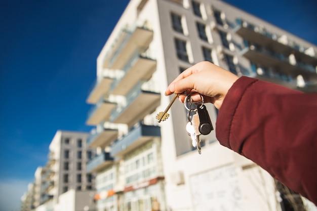 O conceito de comprar um apartamento novo. a mão da mulher segura as chaves de um novo apartamento.