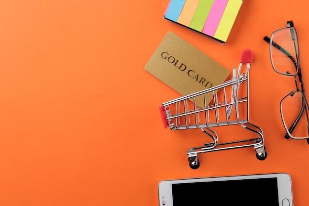O conceito de compras online. composição com cartão de desconto e telefone em fundo laranja