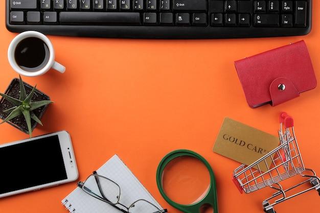 O conceito de compras online. composição com cartões de desconto e carrinho de compras e telefone em fundo laranja