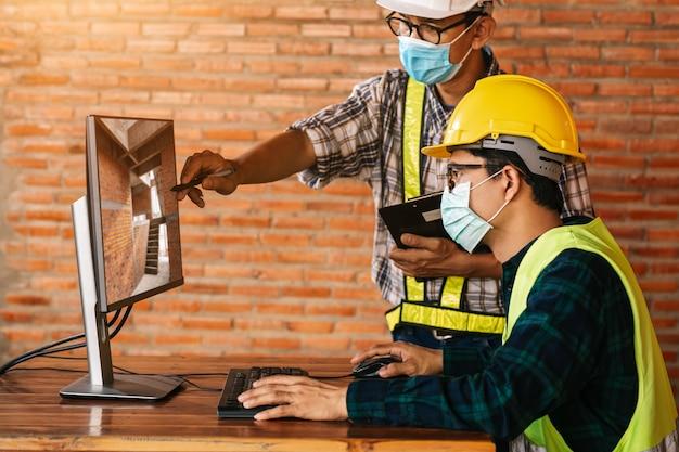 O conceito de construção de engenheiro e arquiteto deve usar máscaras médicas trabalhando no monitor do canteiro de obras via para revisão devido ao impacto global do covid-19 e do distanciamento social.
