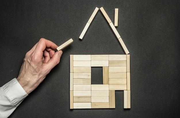 O conceito de construção de uma casa em forma de blocos de madeira.