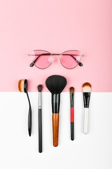O conceito de cosméticos femininos. meios improvisados femininos. conjunto de cosméticos coloridos em um rosa. configuração plana.