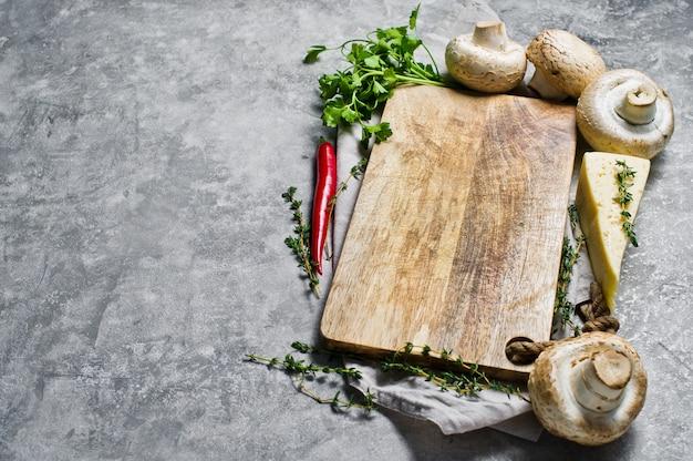 O conceito de cozinhar cogumelos cozidos placa de corte de madeira e ingredientes: pimenta, tomilho, queijo, coentro, cogumelos