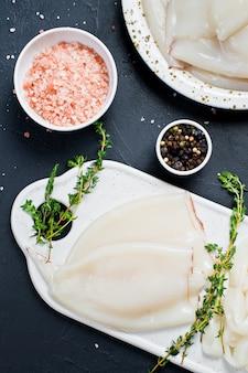 O conceito de cozinhar lula crua ingredientes para cozinhar tomilho, pimenta, sal rosa