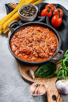 O conceito de cozinhar macarrão à bolonhesa macarrão com tomate, queijo e manjericão. fundo cinza. vista do topo