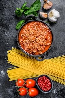O conceito de cozinhar macarrão espaguete com tomate, molho à bolonhesa, queijo e manjericão. fundo preto. vista do topo