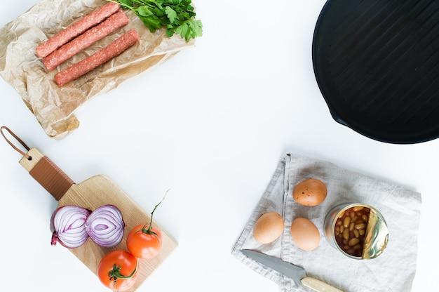 O conceito de cozinhar um café da manhã inglês em um fundo branco e espaço para o texto.
