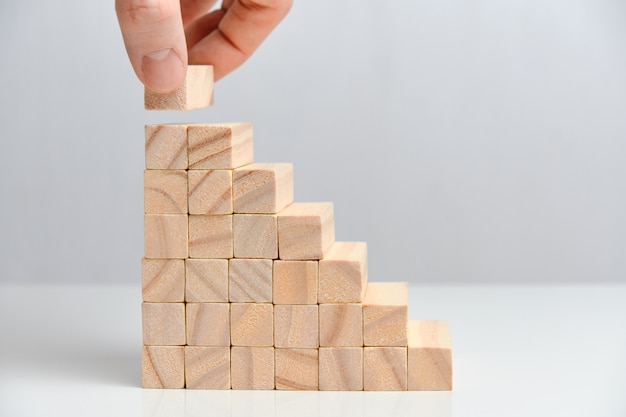 O conceito de criação de uma grande corporação de negócios. mão segura blocos de madeira em um espaço em branco.