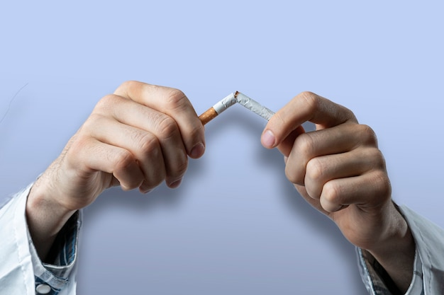 O conceito de dependência do tabaco, pare e pare de fumar nicotina, travando um cigarro com a mão isolado