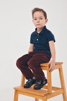O conceito de descanso diário, relaxamento, consideração - o garoto descansa sentado em uma cadeira. expressão calma do rosto do homem, postura relaxada