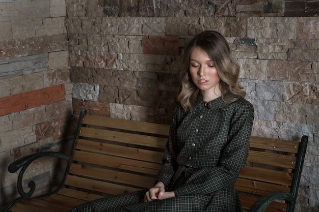 O conceito de descanso do dia, relaxamento, consideração - a menina descansa sentado em uma cadeira. expressão calma do rosto da mulher, postura relaxada