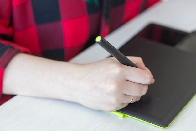 O conceito de designer e animador de negócios fecha a mão do designer gráfico desenhando no tablet