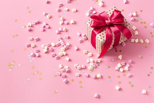O conceito de dia dos namorados. caixa de presente com laço vermelho na parede rosa.