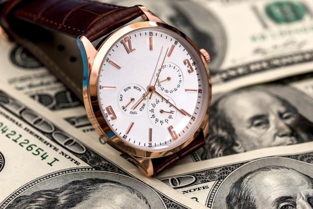 O conceito de dinheiro com um relógio portátil e notas de dólar