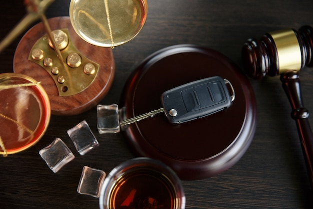 O conceito de dui. martelo de lei, álcool e chaves do carro na mesa de madeira, fundo escuro