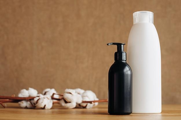 O conceito de eco-cleaning. embalagem de plástico branco e preto de sabão em pó, pó líquido, condicionador, tira-manchas, flores de algodão sobre fundo bege. produto bio orgânico