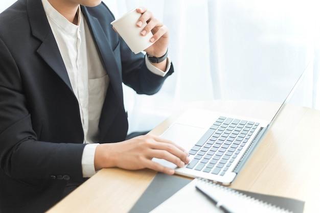 O conceito de empreendedor é um empresário inteligente trabalhando em seu trabalho com seus dispositivos enquanto desfruta de uma bebida.